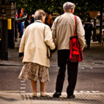 An elderly couple crosses the street hand in hand. Photo by garryknight.