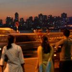 Pedestrians watch traffic in Mumbai