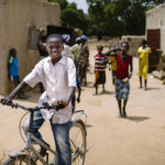 Boy on bicycle in Burkina Faso. Photo by Olivier Girard/CIFOR. Cropped.