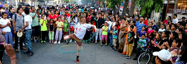 A street performer attracts a crowd of people during her hula-hoop act. Photo by Anil Patel/Facebook.